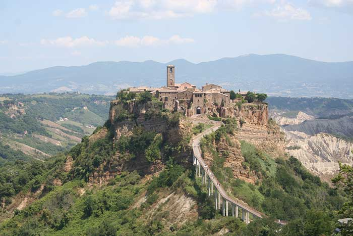 Civita di Bagnoregio, is noted for its striking position atop a plateau of friable volcanic tuff overlooking the Tiber river valley, in constant danger of destruction as its edges fall off, leaving the buildings built on the plateau to crumble.